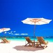 Wooden chairs and umbrellas on white sand beach facing the lagoon — Stock Photo