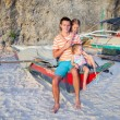 Young dad and his two little girls on a boat at the beach — Stock Photo #39593577