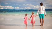 Arrière de deux petites filles, jeune père sur la plage tropicale de blanc — Photo