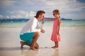 Daddy kissing the hand of his little daughter on exotic beach — Stock Photo