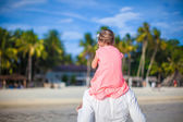 Little girl riding on her dad walking by the beach — Stock Photo