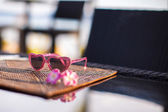 Closeup children sunglasses on the table in tropical resort — Stock fotografie