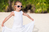 Portrait little adorable girl in white long dress on a tropical beach — Stock Photo