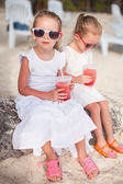 Adorable little girl drinking fresh watermelon on the beach — Stock Photo