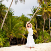 Little adorable girl in white long dress on a tropical beach — Stock Photo