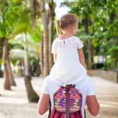 Little girl riding on her dad walking in the jungle — Stock Photo