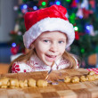 Funny little girl baking Christmas gingerbread cookies — Stock Photo