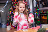 Adorable little girl in wore mittens baking Christmas gingerbread cookies — Stock Photo