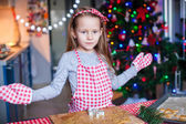 Happy little girl in wore mittens baking Christmas gingerbread cookies — Stock Photo