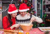 Happy family in Santa hats baking Christmas gingerbread cookies together — Stock Photo