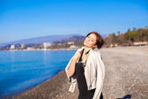 Beautiful young woman relax on the beach in winter sunny day alone — Stock Photo