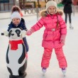 Two adorable little girls skating at the ice-rink — Zdjęcie stockowe