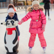 Two adorable little girls skating at the ice-rink — Stok fotoğraf