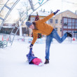 Stock Photo: Young funny father and adorable little girl on a skating rink