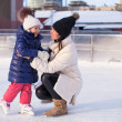 Smiling young mother and her cute little daughter ice skating together — Stok fotoğraf