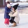 Young mother and her cute little daughter on a skating rink — Stockfoto