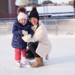 Smiling young mother and her cute little daughter ice skating together — 图库照片