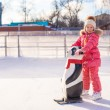 Stock Photo: Little cheerful girl learning to skate on the rink