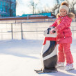 Little cheerful girl learning to skate on the rink — Stock Photo