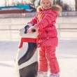 Little happy girl learning to skate on the rink — Stock Photo
