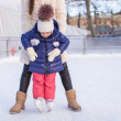 Little adorable girl with her mom learning to skate — Stock Photo