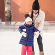 Happy excited little girl and her young mother learning ice-skating — 图库照片
