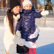Young mother and her cute little daughter on a skating rink — Photo