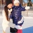 Young mother and her cute little daughter on a skating rink — Stok fotoğraf
