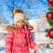 Portrait of adorable little girl near Christmas tree on skating rink — Stock Photo
