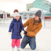 Young father and adorable little girl on a skating rink — Stock Photo