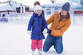 Young happy father and adorable little girl on a skating rink — Stock Photo
