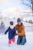 Young Dad teaching his little daughter to skate on the rink — Stock Photo
