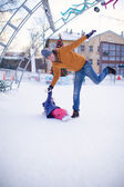 Young funny father and adorable little girl on a skating rink — Stock Photo