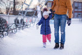 Closeup of adorable little girl with young dad on skating rink — Stock Photo