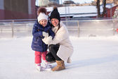 Smiling young mother and her cute little daughter ice skating together — Stock Photo