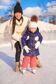 Happy adorable little girl and young mother learning ice-skating — Stock Photo