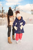 Young mother teaching her little daughter to skate on ice-rink — Stock Photo
