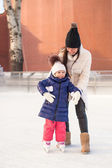 Happy excited little girl and her young mother learning ice-skating — Stockfoto
