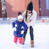 Happy excited little girl and her young mother learning ice-skating — Stock Photo