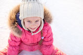 Happy adorable girl sitting on ice with skates after the fall — Stockfoto