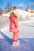 Adorable little girl skating on the ice-rink — Stock Photo