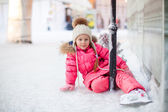 Happy adorable girl sitting on ice with skates after the fall — Stock Photo