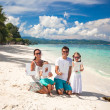 Young happy family of four on tropical vacation with word LOVE — Stock Photo