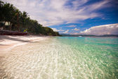 Tropical beach with white sand and a small boat — Stock Photo