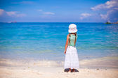 Rear view of little girl in hat looking at the sea on white sand beach — Stock Photo