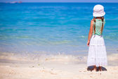 Back view of adorable little girl on an exotic beach — Stock Photo