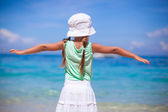 Back view of beautiful little girl spread her arms on an exotic beach — Stock Photo
