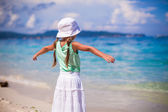 Adorable happy little girl on beach vacation walking squaring arm — Stock Photo
