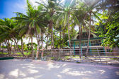 Abandoned and deserted hotel in the jungle on white beach — Stock Photo