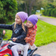 Adorable little girls riding on kid's bike in the green park — Stock Photo